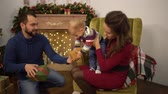 сочельник : Mother, father and little baby sitting in the room with christmas decoration. The man gives small present box to the child sitting on mother laps. Happy family celebrating Christmas together
