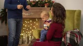first child : Mother, father and little baby are in the room with christmas decoration. Man talking with his wife gesticulating while child jumping on mother laps. Happy family celebrating Christmas