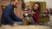 сочельник : Mother, father and little baby sitting on the floor in the room with christmas decoration. Man gives small present box to child crawling on fluffy carpet. Happy family celebrating Christmas together Стоковые видеозаписи