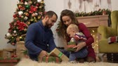 сочельник : Mother, father and little baby sitting on the floor in the room with Christmas decoration. Child playing with present gift boxes lying on the fluffy carpet. Happy family celebrating Christmas together Стоковые видеозаписи