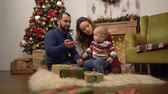first child : Mother, father and little baby sitting on the floor in the room with christmas decoration. Dad playing with child, holding toy orange slice in hand. Happy family celebrating Christmas together
