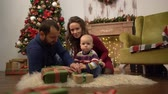 сочельник : Happy family celebrating Christmas together Mother, father and little baby sitting on the floor in the room with Christmas decoration. Child playing with present gift boxes lying on the fluffy carpet. Стоковые видеозаписи