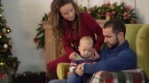 сочельник : Mother, father and little baby are in the room with christmas decoration. Man holding little son on his laps, woman bends and kisses her husband. Happy family celebrating Christmas together Стоковые видеозаписи