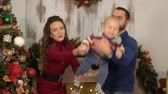 first child : Mother, father and a baby have a fun in the room with christmas decoration. Dad and mom playing with child, throws him up holding in arms. Happy family celebrating Christmas together