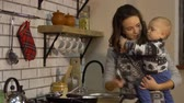 first child : Pretty young woman with a baby in her arms in modern kitchen preparing breakfast. Lady pours salt into the frying pan cooking food. Happy family concept