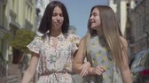 casual clothing : Two joyful women with shopping bags walking through city street. Young girls wearing stylish summer dresses enjoying spending time together. Shopping lifestyle concept.