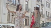 spacer : Two happy girlfriends after shopping with shopping bags taking selfie on cellphone with new clothes outdoors. Leisure of happy girls. Carefree ladies walking through city street.
