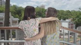 conserva : Two attractive girls standing outdoors together hugging and talking, admiring beautiful cityscape. Girlfriends talking about everyday matters. Summertime leisure. Back view