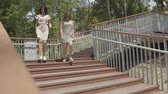 запустить : Two attractive girls wearing summer dresses running down the stairs in the city park. Carefree girlfriends having fun outdoors. Summertime leisure of girlfriends.