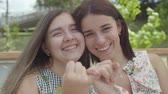 conserva : Portrait two cute girls taking each others little fingers and smiling, looking in the camera. Conciliatory gesture, friendship concept. Summertime leisure. Vídeos