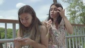 conta : Emotional young woman telling her story to her friend, but she does not listen, texting on the cellphone sitting outdoors. Cute student sharing the problem with her friend, actively gesturing