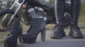 spiked : The young woman changing her motorcycle shoes on spiked shoes with high heels close-up. Brutality and femininity concept. Leisure and travel by motorcycle. Stock Footage