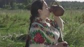 scythe : Adorable overweight woman enjoys drinking fresh milk from the earthen jug on the green summer field. Beautiful landscape. Folklore, traditions concept. Real rural woman. Slow motion