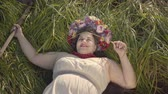 scythe : Portrait of carefree overweight woman with a wreath on her head lying on the grass in summer field holding the scythe. Connection with nature, rural life.
