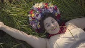scythe : Portrait of carefree smiling overweight woman with a wreath on her head lying on the grass in summer field near the scythe. Connection with nature, rural life