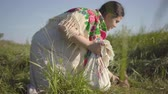 mendil : Beautiful overweight woman sitting in wild grass with the earthen jar and spreading a handkerchief with food preparing to eat. Traditions concept, connection with nature. Country lifestyle