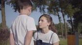 Strict older sister scolding her younger brother in the summer park. Relationship between siblings. Naughty boy walking with his sister outdoors. Stock Footage