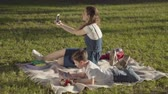 spring : Older sister spending time with younger brother outdoors. The boy reading the book and girl taking selfie in the park. Summer leisure. Gadget addiction