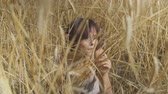 Graceful fashion woman with short hair smoking cigarette sitting among the wheat field looking away. Confident carefree girl outdoors. Real people series. Stock Footage