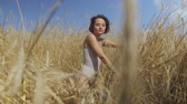 free country : Chic woman with short hair wearing bodysuit relaxing on the wheat field. Girl enjoys nature looking and posing at the camera. Confident carefree girl outdoors. Real people series Stock Footage