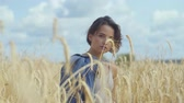 Portrait adorable woman with short hair relaxing on the wheat field. Girl enjoys nature looking and posing at the camera. Confident carefree girl outdoors. Real people series