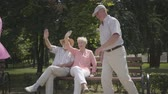 pensão : Two senior men and one woman waving hands while their friend woman driving on scooter in the park. Mature people resting outdoors, active lifestyle. Cheerful senior retired people. Vídeos
