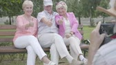 pensão : Old man in a hat makes a photo of his friends sitting on a bench in the park. Two adorable joy women and man resting outdoors together. Cheerful senior retired people.