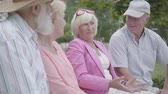 друг : Two cute mature couples talking and smiling sitting on the bench in the summer park. Double date of senior couples. Friendly company resting outdoors. Old men and women met together. Retired people. Стоковые видеозаписи