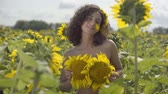 slunečnice : Portrait of pretty curly playful girl looking at the camera smiling standing in the sunflower field. Bright yellow color. The girl covers herself with sunflowers. Freedom concept. Happy woman outdoors