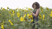 枝編み細工 : Cute slim girl walking and picking flowers in the big wicker basket in the sunflower field. Connection with nature. Bright yellow color. Happy woman outdoors. Rural life
