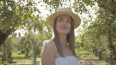 Attractive young woman in straw hat and long white dress looking at the camera smiling standing in the green summer garden. Camera moving away Wideo