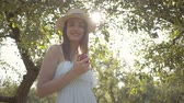 Attractive young woman in straw hat and long white dress looking at the camera holding apple standing in the green summer garden. Harvest time, rural lifestyle Wideo