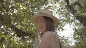 Portrait of attractive young woman in straw hat and long white dress looking at camera while picking apples standing on a ladder in the green garden. Harvest time, rural lifestyle Wideo