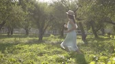 Cute young woman in straw hat and long white dress running through the green summer garden. Carefree rural life, connection with nature. Wideo