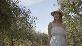 Attractive young smiling woman in straw hat and long white dress walking through the green summer garden. Carefree rural life, connection with nature. Front view