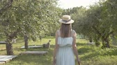Attractive young woman in straw hat and long white dress walking through the green summer garden. Carefree rural life, connection with nature. Back view Wideo