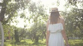 Back view of pretty young woman in straw hat and long white dress walking through the green summer garden. Carefree rural life, connection with nature. Wideo
