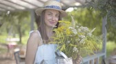 Portrait pretty young woman in straw hat and white dress looking at the camera smiling while holding wild flowers. Rural lifestyle.