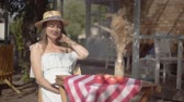 Young girl in a straw hat and white dress sitting at the small table and looking at the camera. Rural lifestyle. Leisure on a beautiful summer day.