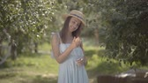 Pretty fashion young positive woman in straw hat and white dress looking at the camera smiling holding apple standing in the green summer garden. Harvest time, rural lifestyle