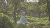 Adorable young woman in straw hat and long white dress running through the green summer garden. Carefree rural life, connection with nature. Slow motion.