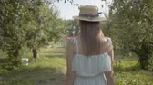 Back view of attractive young woman in straw hat and long white dress walking through the green summer garden then turning and making inviting gesture. Carefree rural life, connection with nature Wideo