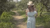 Back view of attractive young woman in straw hat and long white dress running through the green summer garden then turning and making inviting gesture. Carefree rural life. Slow motion