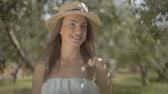 Portrait fashion young woman in straw hat and long white dress looking at the camera smiling standing in the green summer garden holding bunch of dry grass. Rural lifestyle. Slow motion