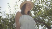 Cute young woman in straw hat and white dress picking apples and putting in the wicker basket in the green garden. Harvest time, rural lifestyle. Bottom view. Slow motion Wideo