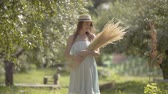 Cute fashion young woman in straw hat and long white dress looking at the camera smiling standing in the green summer garden holding bunch of grass. Rural lifestyle.