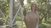 vime : Attractive young woman in straw hat holding the wicker basket with herbs and looking at the camera smiling in the green summer garden. Rural lifestyle. Slow motion