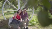 даты : Cute young woman and man sitting in the garden the guy hugging his girlfriend. Emotional woman telling her boyfriend interesting story. The relationship between husband and wife. Happy routine life