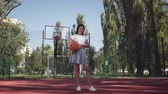 célok : Adorable teen brunette girl holding a basketball ball looking at the camera standing on the basketball court outdoors. Concept of sport, power, competition, active lifestyle. Sports and recreation.
