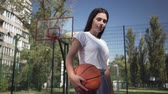 sportos : Portrait young brunette girl holding a basketball ball looking at the camera standing on the basketball court outdoors. Concept of sport, power, competition, active lifestyle. Sports and recreation. Stock mozgókép